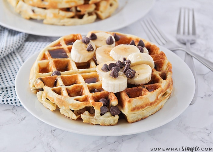 a plate with a fluffy chocolate chip waffle topped with syrup, bananas and chocolate chips