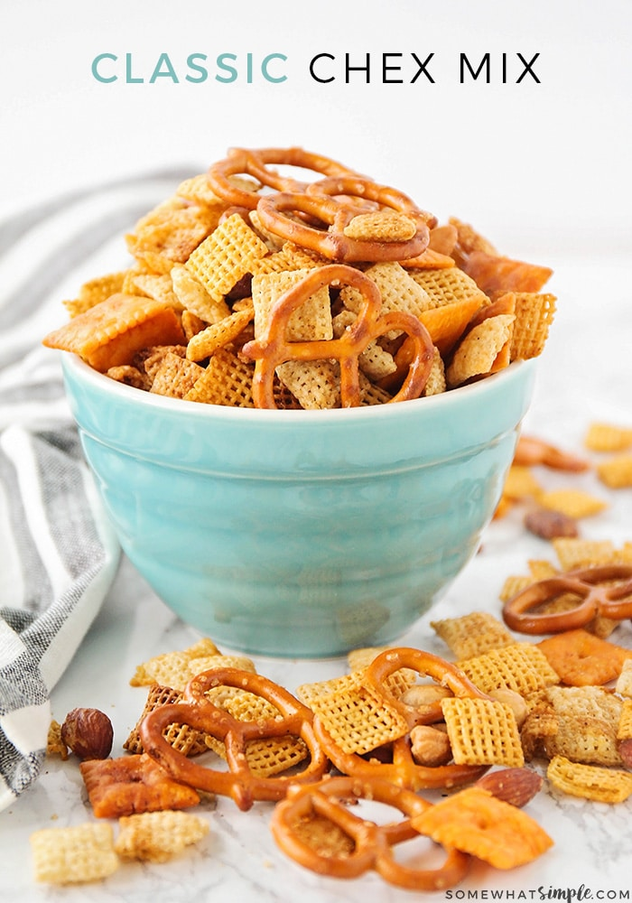 a blue bowl full of overflowing homemade original chex mix, with more chex mix on the counter top, using this simple recipe