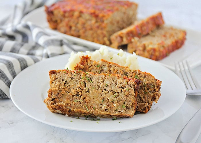 two slices of meatloaf on a white plate made with this simple meatloaf recipe. A loaf on a serving tray is in the background.