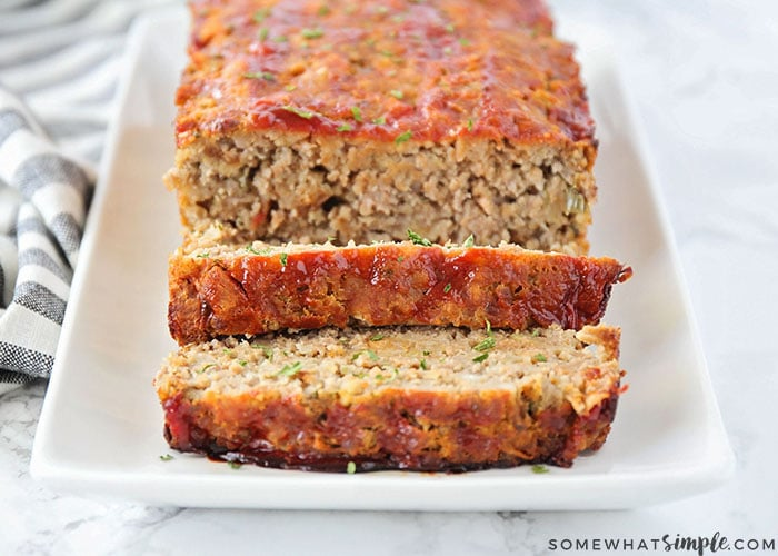a loaf of the best meatloaf recipe on a white serving tray with two slices cut and layered in the front of the loaf
