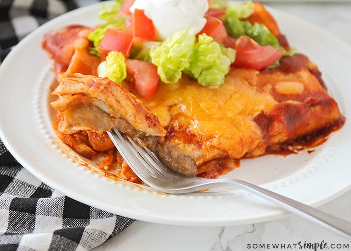 two enchilada style baked bean burritos on a plate topped with lettuce and tomatoes. A fork has cut a bit off the corner and is laying on the plate with the piece of burrito stuck to the fork.