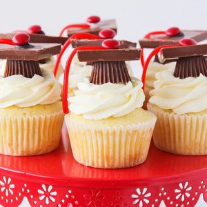 a red cake stand with seven graduation cupcakes on it. They are vanilla cupcakes with vanilla frosting that have graduation toppers made with peanut butter cups, squares of chocolate, red candies and thin red licorice