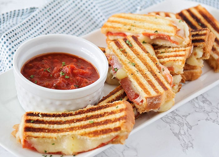 pizza grilled cheese sandwiches on a white serving dish with a marinara dipping sauce is an easy super bowl snack food idea