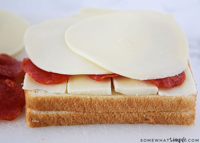 a slice of white bread topped with cheese and pepperoni is the first step to make a grilled cheese dipper
