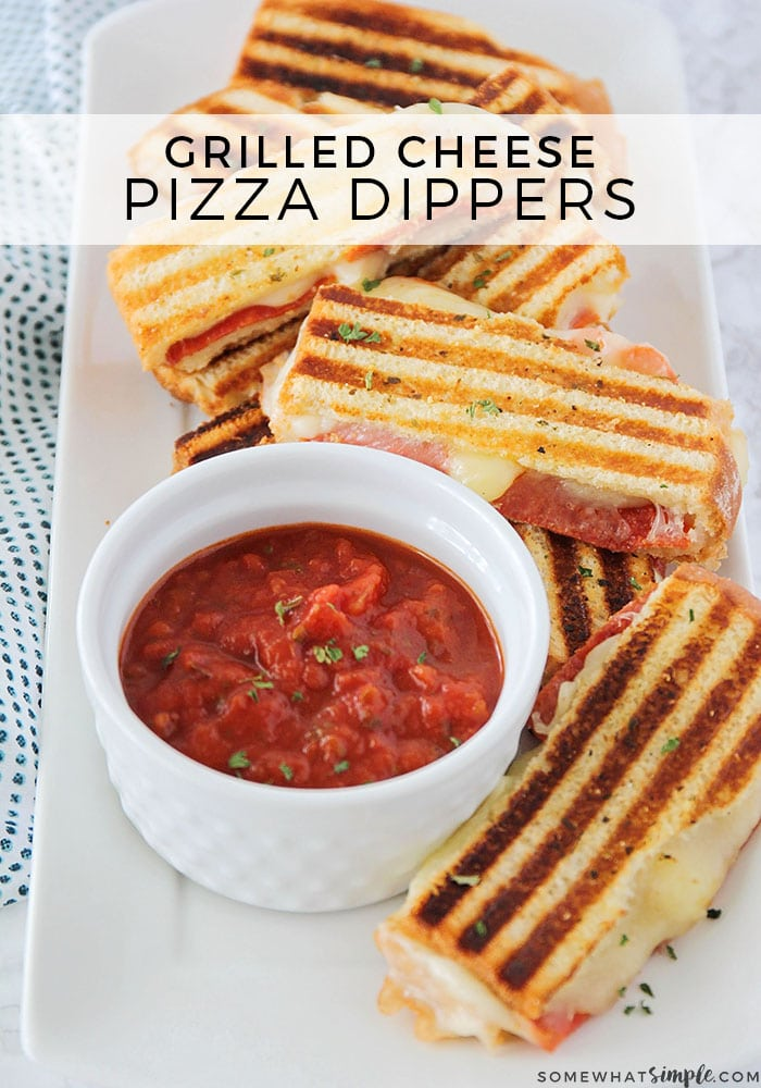 a long white tray with several pizza dippers on it with a small bowl of marinara sauce and the words grilled cheese pizza dippers is written at the top of the image in a white translucent box