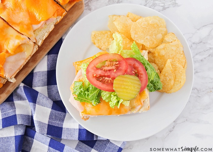 an open faced baked sandwiches on a plate with potato chips is a simple snack to serve during the super bowl