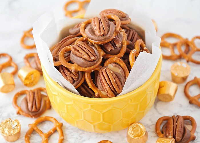 a yellow bowl full of rolo pretzel turtles with more pecans and individual rolos on a table