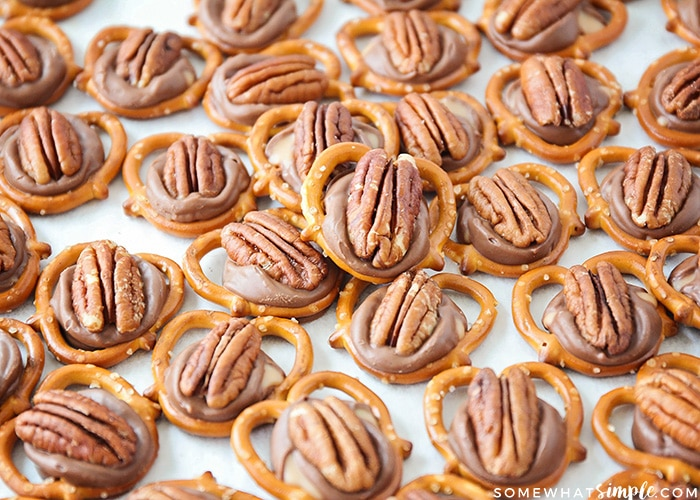 a tray full of baked pretzel rolo pecan turtles