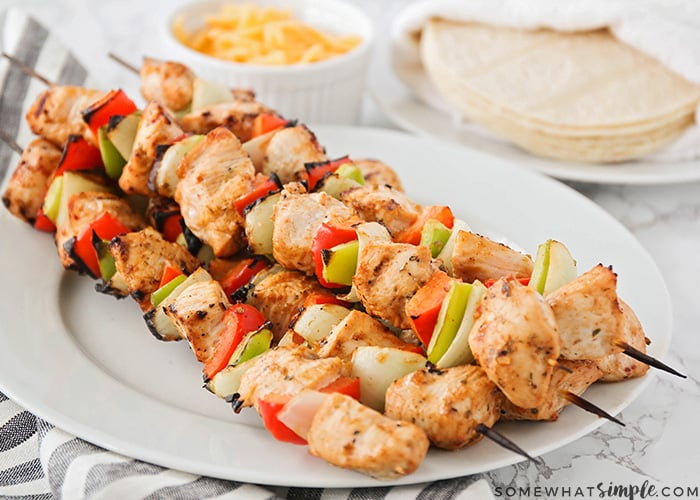 a plate full of grilled chicken skewers that have green and red bell peppers and onions. Behind the plate is a plate of tortillas and a small white dish of cheddar cheese.