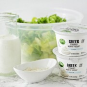 a jar of homemade ranch dressing that's next to a tub of Greek yogurt and a bowl of lettuce