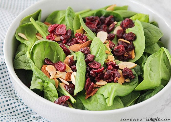 a close up of a bowl filled with baby green spinach, cranberries and sliced almonds