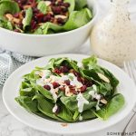 a plate filled with a spinach salad with cranberries and topped with almonds and a homemade poppy seed dressing.