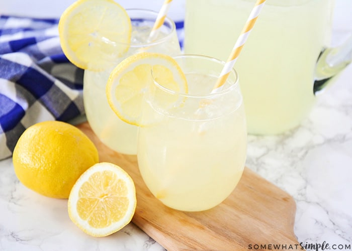 two glasses and a pitcher filled with homemade lemonade with a couple of lemons laying on the counter