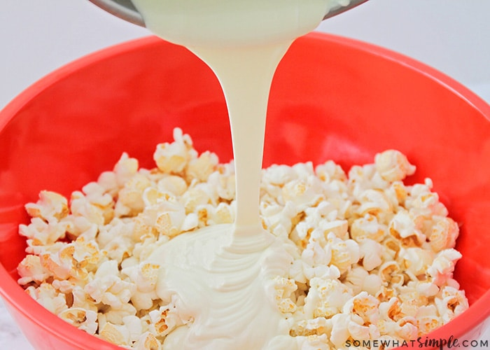 melted white chocolate being poured over popcorn