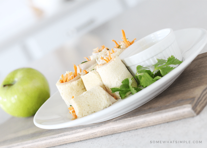 a white plate with several sandwich sushi rolls with a side of ranch sitting on a cutting board with a green apple next to the plate