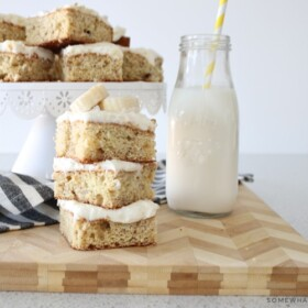 a stack of banana bars topped with cream cheese frosting and sliced bananas