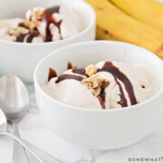 two white bowls filled with frozen banana ice cream topped with chocolate syrup and nuts. On the counter next to the bowls are two spoons and a small bunch of bananas