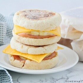 Two make ahead breakfast sandwiches stacked on top of each other on a white plate. Each one is made with an English muffing, American cheese, eggs, and Canadian bacon. Behind the plate are three more sandwiches wrapped in parchment paper.