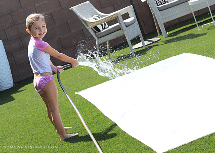 a little girl spraying a homemade slip and slide with water from a hose