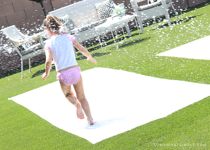 a little girl running through spraying water on a diy slip and slide made from a plastic drop cloth