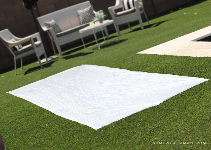 a plastic drop cloth on grass that will be used as a DIY slip and slide