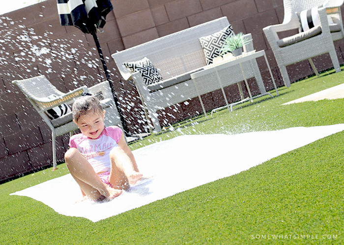 a little girl sliding through spraying water on a diy slip and slide in her backyard
