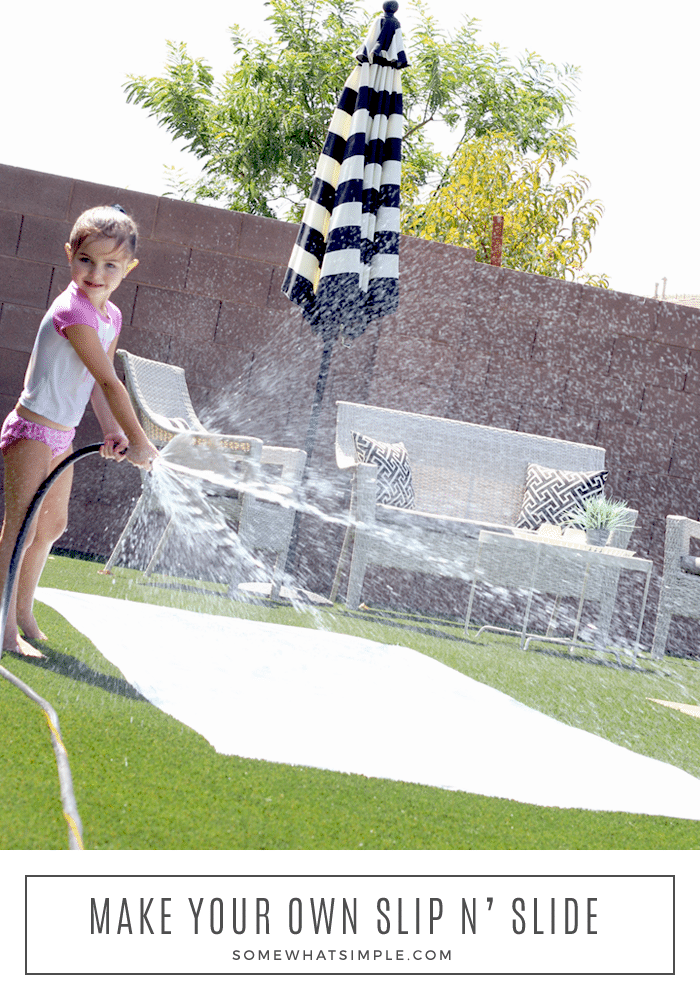 a little girl spraying water from a hose on her homemade slip and slide