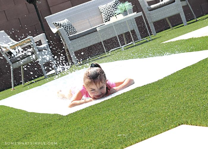 a little girl sliding on a homemade slip and slide