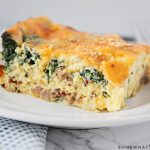 a square of spinach and egg casserole on a white plate. The casserole is topped with bread crumbs and cheese.