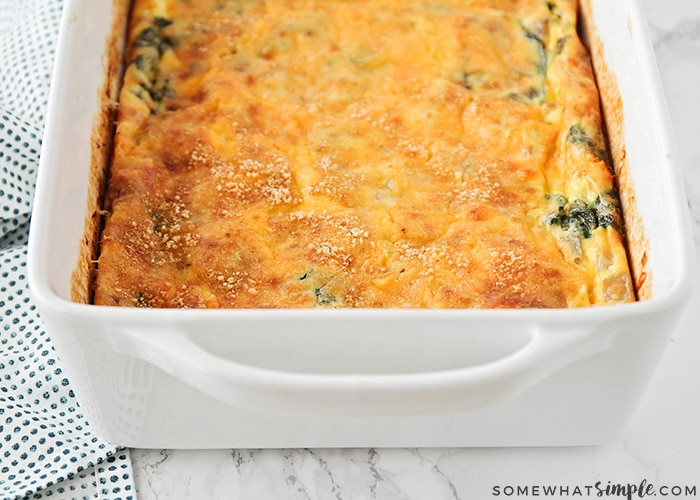 a baked egg and spinach casserole that just came out of the oven and the cheese on top is a golden brown color.