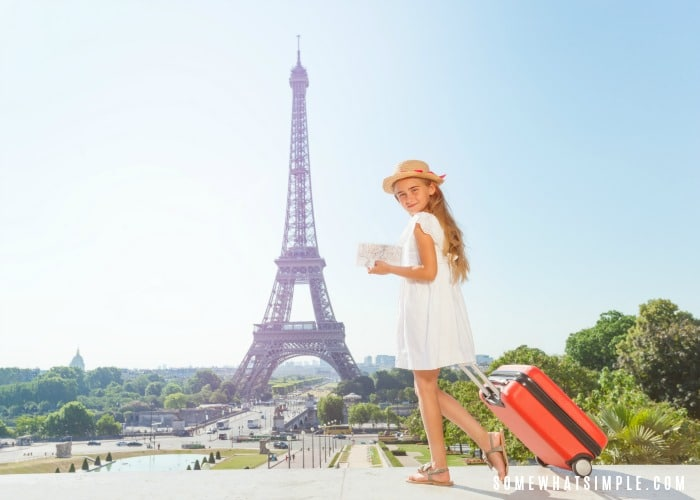 a girl in a white dress pulling a rolling suitcase in one hand and holding a packing list in the other. The Eiffel Tower is in the background.