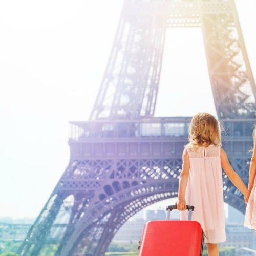 two young girls in pick dresses standing in front of the Eiffel Tower. The younger one has a red suitcase filled items from a packing list for europe.