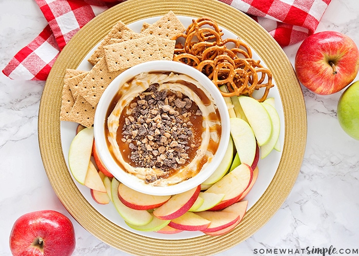 looking down on a bowl of caramel dip made with cream cheese surrounded by apple slices, graham crackers and pretzels on a serving dish