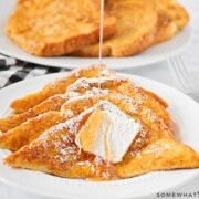 four slices of pumpkin french toast on a plate topped with a pad of butter and syrup being drizzled over the top