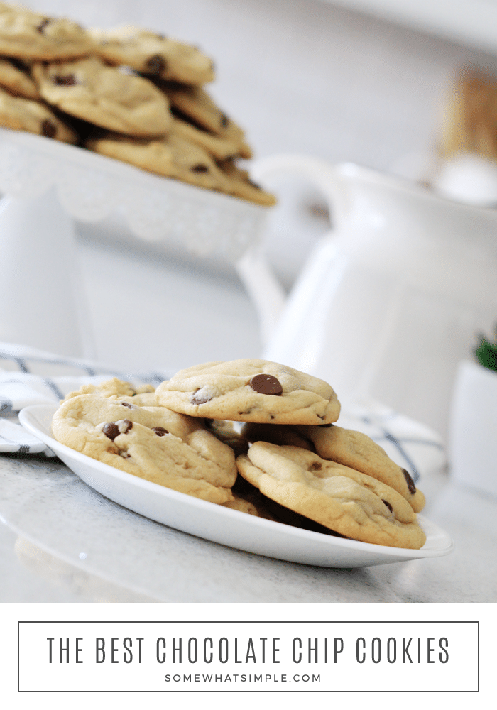 a white plate filled with homemade chocolate chip cookies made using this easy recipe. Behind the plate is a cake stand with more soft and chewy cookies piled on top. At the bottom of the image is a white box with the words, the best chocolate chip cookies, written inside.