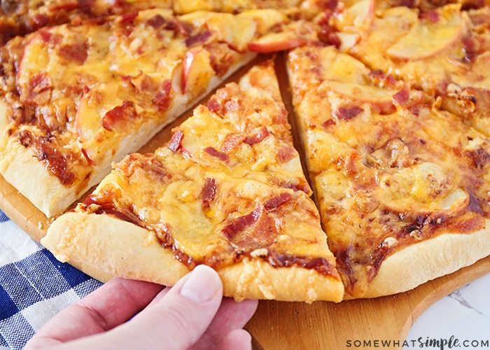 a pizza topped with bacon, cheddar cheese and apple slices