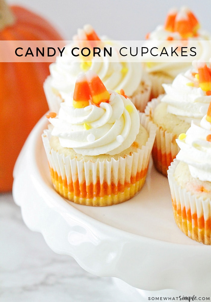 several Candy Corn Cupcakes on a cake stand that are topped with frosting, sprinkles and candy corns