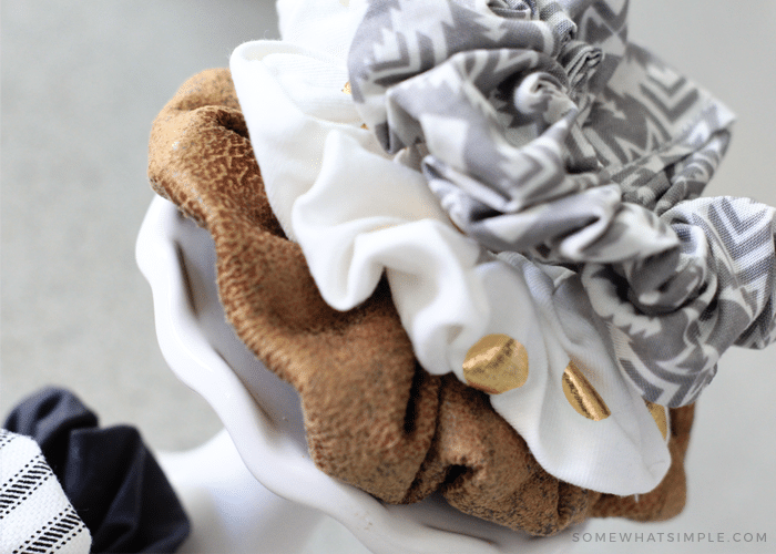 a brown, white and grey scrunchie stacked on top of each other