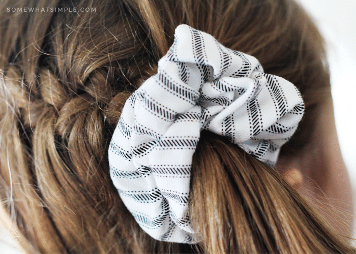 a white and grey striped scrunchie being worn in a pony tail by a young girl
