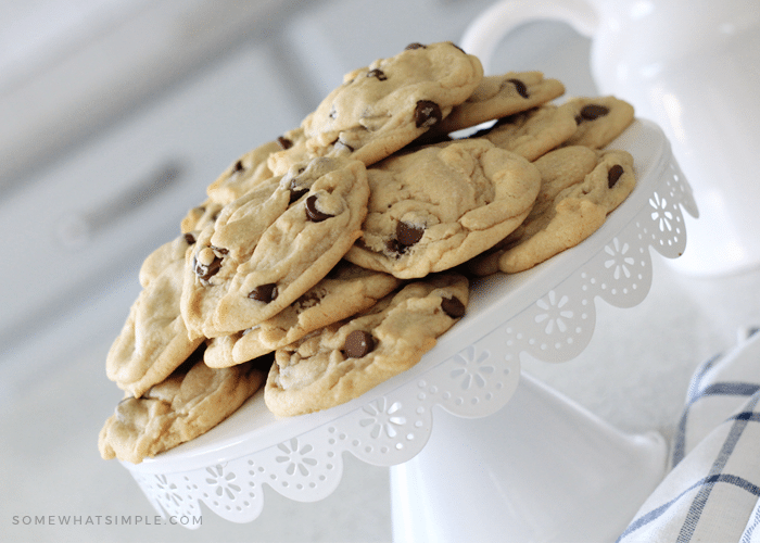 a white cake stand with a mound of chocolate chip cookies on top. They appear thick and soft and are filled with chocolate chips.
