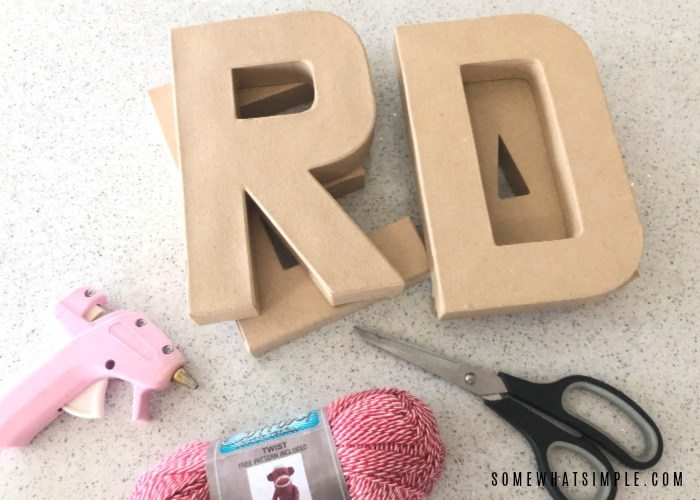 wood letters, yarn, scissors and a glue gun laying on a white counter