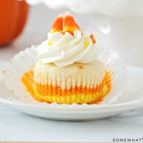 a Candy Corn Cupcake with orange, yellow and white layers on a plate topped with cream cheese frosting