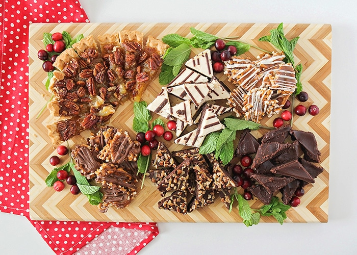 looking down on a wooden Christmas dessert board filled with treats