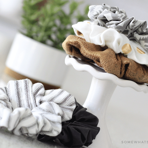 the DIY hair scrunchies stacked on top of each other on a small stand with two more scrunchies lying next to the stand on a counter
