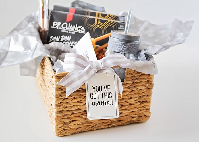 a new mom gift basket filled with gift items wrapped in gray tissue paper and a light grey striped bow with a tag on the front that says you've got this mama!