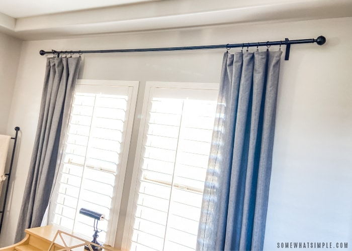 blue drapes hanging next to a window with shutters