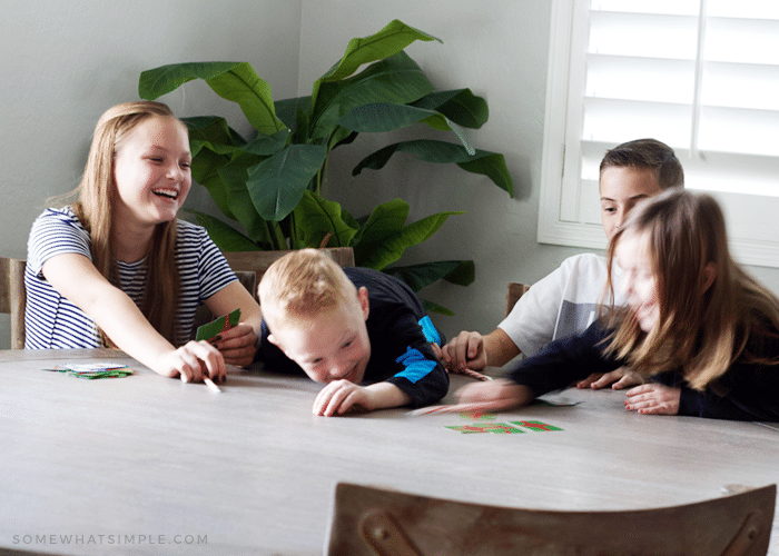 four children sitting at a table learning how to play spoons