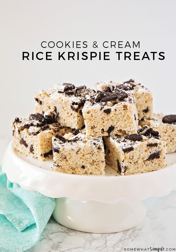a white cake stand with oreo cookie rice krispies stack on top. At the top of the image the words Cookies and Cream Rice Krispie Treats are written in black letters.