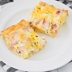 two squares of a croissant breakfast egg casserole made with ham on a white plate sitting on top of a cloth black and white striped napkin.