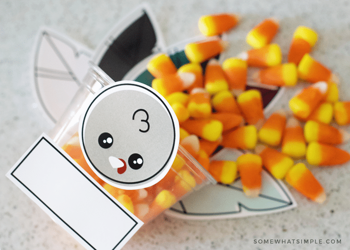 candy corn inside plastic cup with turkey face and feathers taped to the outside